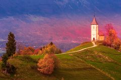 Zonsondergang met kerk bovenop heuvel, Slovenië stock afbeelding