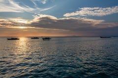 Zonsondergang met kleurrijke hemel en boten op het overzees Royalty-vrije Stock Afbeelding