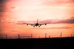 Zonsondergang met landend vliegtuig Stock Foto's