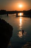 Zonsondergang met roeiers aan de brug Royalty-vrije Stock Afbeelding
