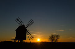 Zonsondergang met silhouet van een oude windmolen Royalty-vrije Stock Afbeeldingen