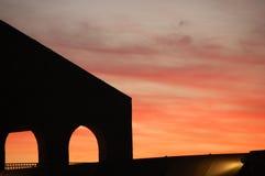 Zonsondergang met silhouet van structuur met bogen royalty-vrije stock afbeelding