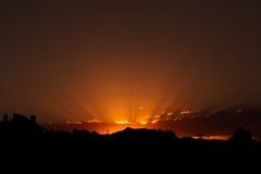 Zonsondergang met silhouetten van huizen Stralen van een zonsondergang op een oranje hemel Schaduwensilhouetten van huizen Royalty-vrije Stock Afbeelding