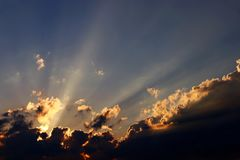 Zonsondergang met stralen van licht achter wolken Stock Afbeeldingen