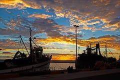 Zonsondergang met twee vissersboten in haven stock fotografie
