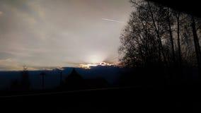Zonsondergang met wolken, bomen en vliegtuig stock afbeelding