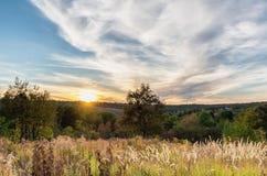 Zonsondergang met wolken in de herfsttijd over kleurrijke heuvel stock foto