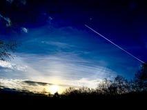Zonsondergang met wolken, vliegtuig en bomen stock foto