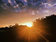 Zonsondergang met zonstralen stock afbeelding