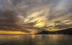 Zonsondergang in Omis Dalmatië met dramatische wolken bij hemel en nachtlichten in stad op de kust bij rechterkant en open zee o stock foto