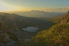 Zonsondergang onder bergmeer Stock Afbeelding