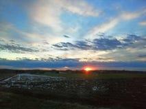 Zonsondergang op de gebieden stock afbeelding