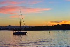 Zonsondergang op de overzeese baai met boot Royalty-vrije Stock Foto's