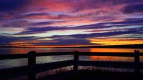 Zonsondergang op de rivier voor een houten omheining royalty-vrije stock foto