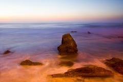 Zonsondergang op de rotsachtige kust in Portugal Stock Foto