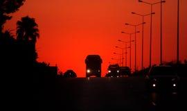 Zonsondergang op een autosnelweg stock foto
