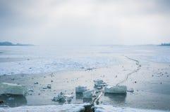 Zonsondergang op een bevroren meer Het mooie zonlicht door de donkere wolken en de koude winter vertroebelen over het bevroren me Stock Foto