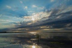 Zonsondergang op een eenzaam strand Stock Foto's