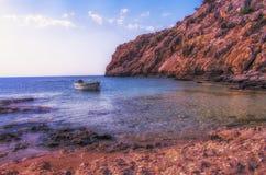 Zonsondergang op een kleine boot en een rotsachtige landtong Royalty-vrije Stock Afbeeldingen