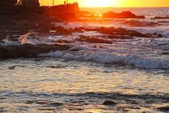 Zonsondergang op een rotsachtig strand Royalty-vrije Stock Afbeelding