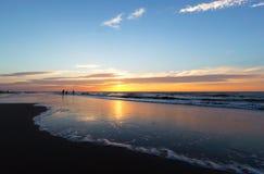 Zonsondergang op een strand stock fotografie
