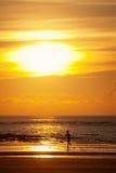 Zonsondergang op een strand met silhouet van een jong geitje Stock Foto's