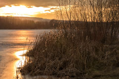 Zonsondergang op het bevroren meer Stock Afbeelding