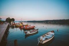 Zonsondergang op het meer lago Di garda op de kust van saloboot dichtbij de pijler op de achtergrond van de oude stad Royalty-vrije Stock Foto's