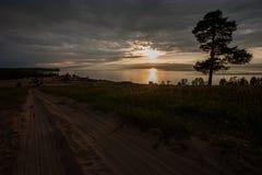 Zonsondergang op het meer met een boom en een zandige weg royalty-vrije stock afbeeldingen