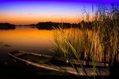 Zonsondergang op het meer met oud bootwrak royalty-vrije stock afbeelding