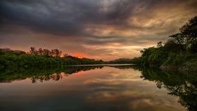 Zonsondergang op het meer met rond bomen royalty-vrije stock foto's