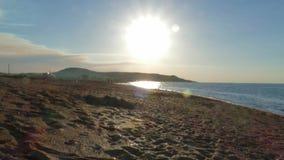 Zonsondergang op het overzeese strand stock videobeelden