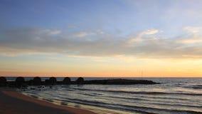 Zonsondergang op het strand met een golfbreker stock footage