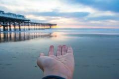 Zonsondergang op het strand met een pijler Blauwe en oranje zonsondergang Zon op het haar Stock Afbeeldingen