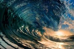 Zonsondergang op het strand met oceaangolf stock foto's