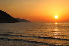Zonsondergang op het strand met verre bergen Royalty-vrije Stock Afbeeldingen