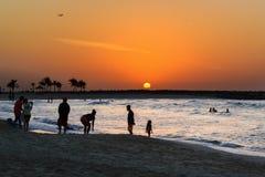 Zonsondergang op het strand Silhouetten van mensen tegen de achtergrond van de het plaatsen zon Royalty-vrije Stock Fotografie