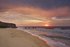 Zonsondergang op het verlaten strand Stock Foto