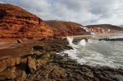 Zonsondergang op klippen met golven het verpletteren stock foto
