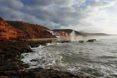 Zonsondergang op klippen met golven het verpletteren stock afbeelding