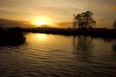 Zonsondergang op riverbank Stock Afbeelding