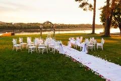 Zonsondergang op rivier Romantische huwelijksceremonie Witte houten stoelen met lint en bloemen op een groen gazon De leunstoelen Royalty-vrije Stock Fotografie