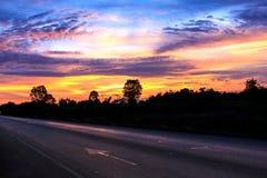 Zonsondergang op weg Stock Foto's