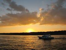 Zonsondergang op zee en boot royalty-vrije stock afbeeldingen
