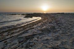 Zonsondergang op zee met zeewier en oude stormlopen Stock Foto