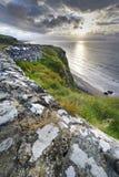 Zonsondergang over bergaf kustlijn stock afbeeldingen