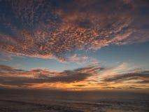 Zonsondergang over de Atlantische Oceaan die een dramatische oranje wolk samenstellen Stock Fotografie