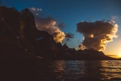 Zonsondergang over de bergen door het overzees Silhouet van de bergen Mooie wolken stock foto