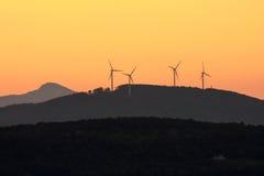 Zonsondergang over de bergen met windturbines stock foto's