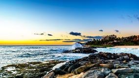 Zonsondergang over de horizon met een paar wolken en rotsachtige kusten van de westkust van Oahu stock afbeeldingen